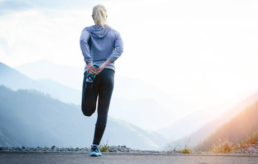 Junge Sportlerin beim Dehnen der Beinmuskulatur