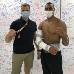 Karateka Jonathan Horne wird von Bauerfeind-Mitarbeiter Marius Jonelis mit der Schulterorthese OmoLoc versorgt.